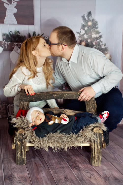 Piękne rodzinne zdjęcie z niemowlakiem śpiącym na drewnianej ławeczce