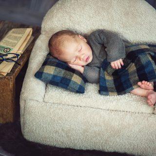 stylizowana sesja noworodkowa, czarny kot studio, noworodek lezący na kanapie, popołudniowa drzenka