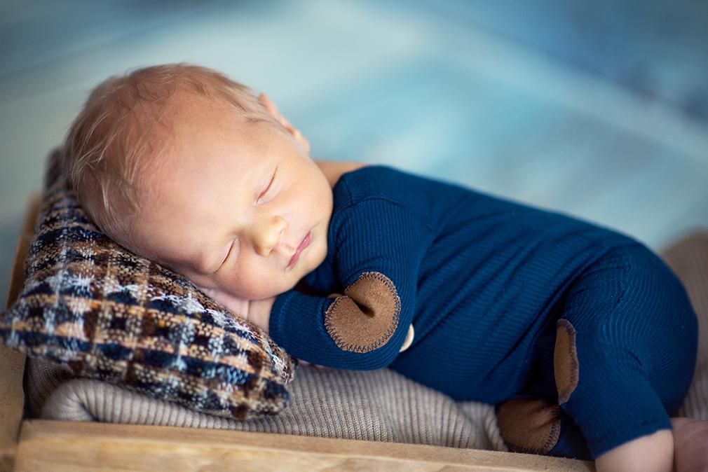 noworodek śpiący na poduszeczce podczas sesji w koninie